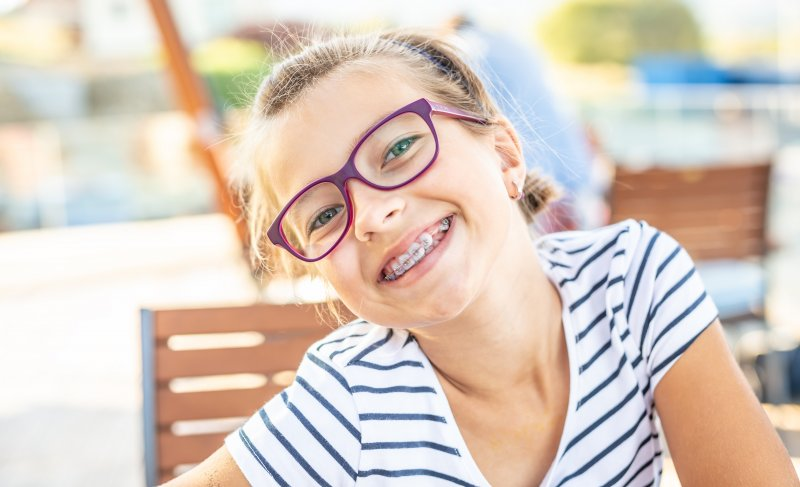 Child smiling with braces outside