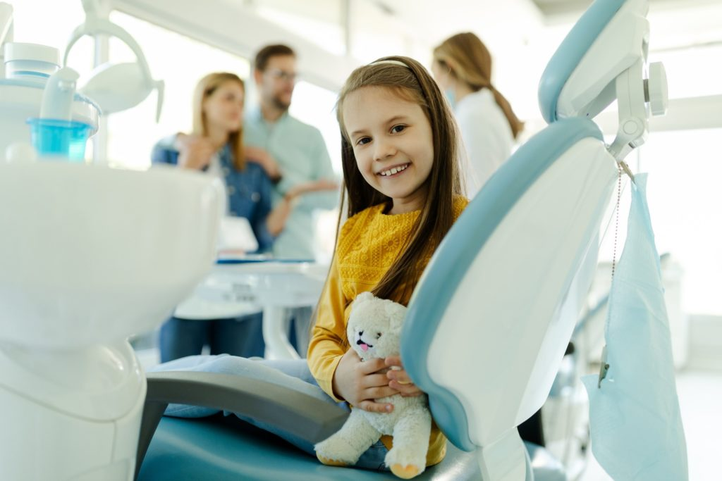 Child smiling while dentist and parents discuss dental sealants
