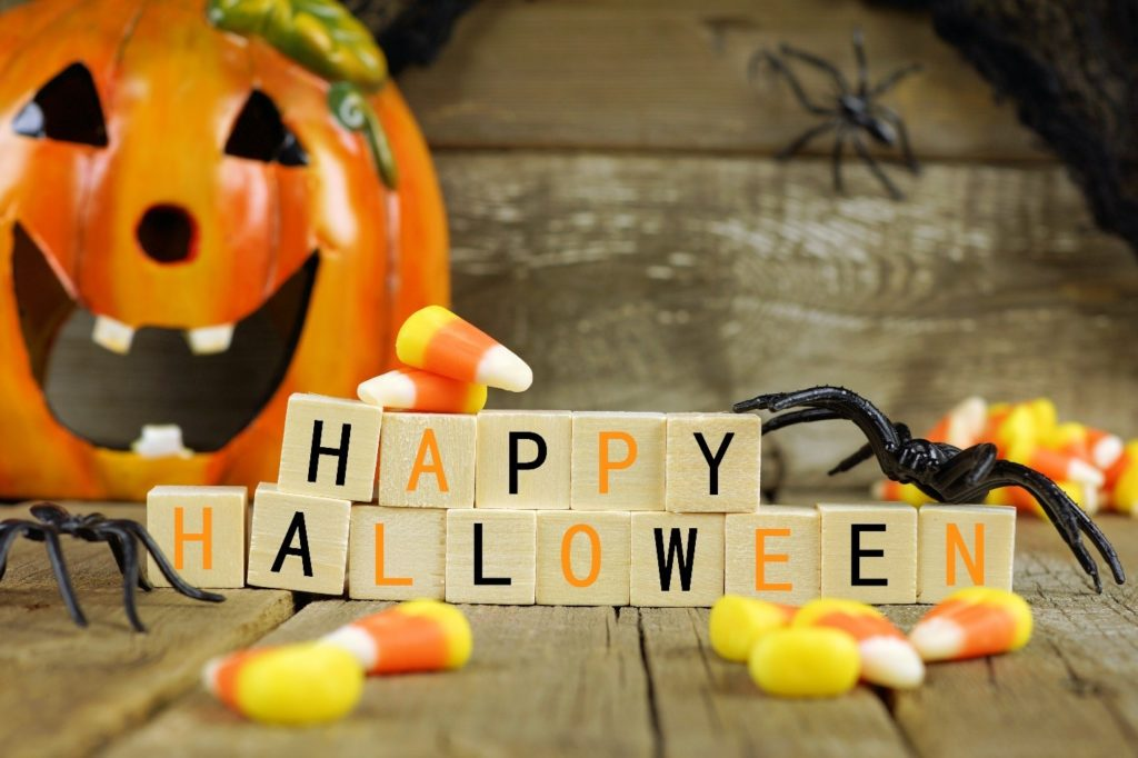 Happy Halloween letter blocks with candy corn, fake spiders, and a pumpkin